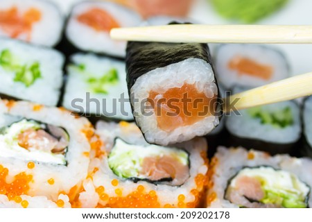 Closeup view of a set of maki sushi. One piece of sushi is in the sushi bars - stock photo