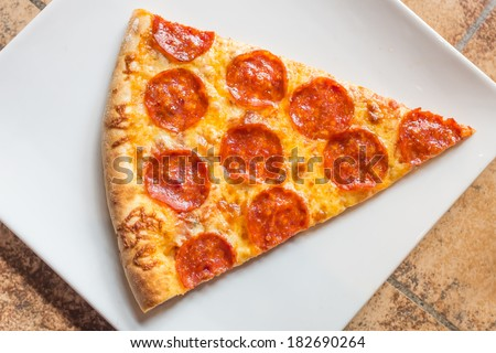 Closeup view of a slice of a pepperoni pizza - stock photo
