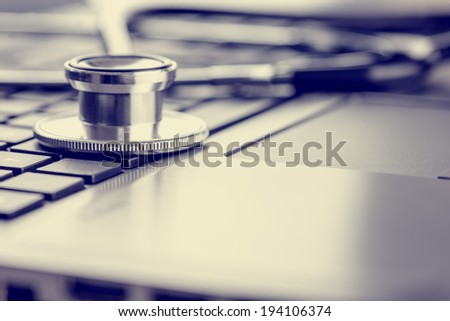 Closeup view of a stethoscope lying on a laptop keyboard depicting online healthcare and medical advice, retro effect faded look.  - stock photo