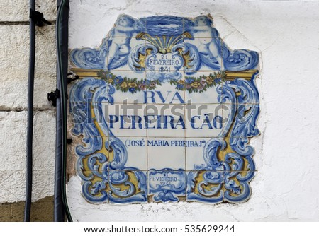 Closeup view of a street name panel made of traditional Portuguese blue tiles in Setubal, Portugal. The street name is: PEREIRA CAO STREET