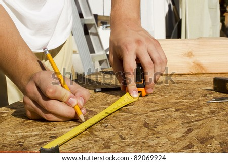 Closeup view of a worker measuring a section of plywood. - stock photo