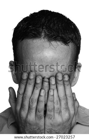 Closeup view of a young man suffering from depression and covering his eyes, done in black and white - stock photo
