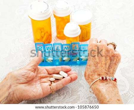 Closeup view of an eighty year old senior woman's hands as she sorts her prescription medicine. - stock photo