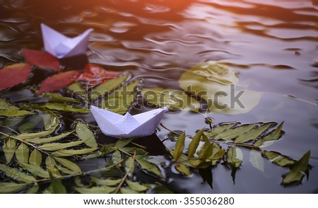 Closeup view of beautiful colorful autumn tree leaves red yellow orange green colors floating on wavy water with reflection of nature with white paper ship on outdoor background, horizontal picture - stock photo