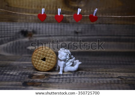 Closeup view of beautiful cupid angel decorative figurine near red paper greeting valentine clothes-peg in shape of heart with round pastry on wooden background copy space, horizontal picture - stock photo