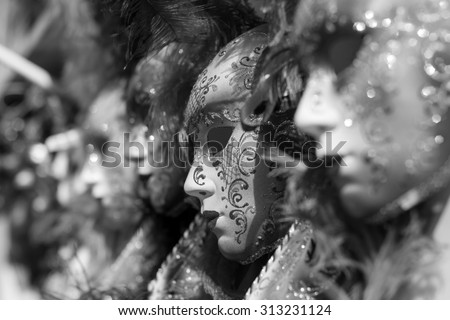 Closeup view of beautiful ornate venetian carnival red mask with golden pattern. Black and white photography. - stock photo