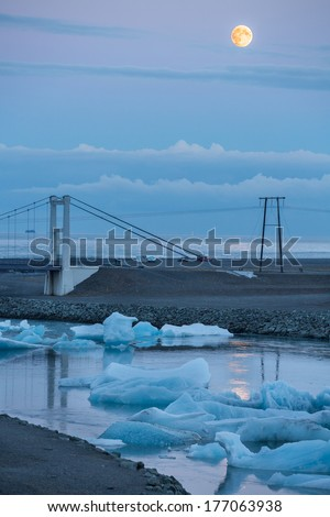 Closeup view of bridge in Jokulsarlon glacial lagoon estuary at dusk with full moon, Iceland