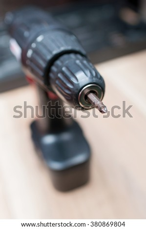 Closeup view of cordless drill with fastener bit on wooden table in carpentry - stock photo