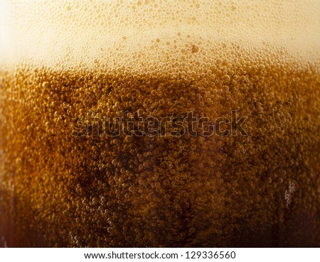 Closeup view of dark beer pouring into the glass - stock photo