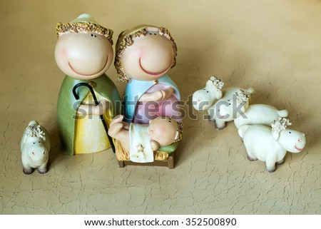 Closeup view of decorative celebrating Christmas and Jesus birth figurines of holy virgin Mary Joseph newborn child with few white sheeps standing on light leather background, horizontal picture - stock photo