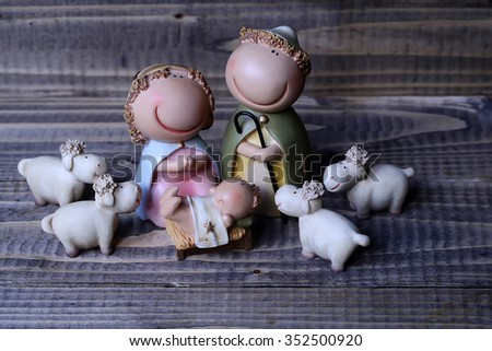 Closeup view of decorative celebrating Christmas and Jesus birth figurines of holy virgin Mary Joseph newborn child with few white sheeps standing on wooden background, horizontal picture - stock photo