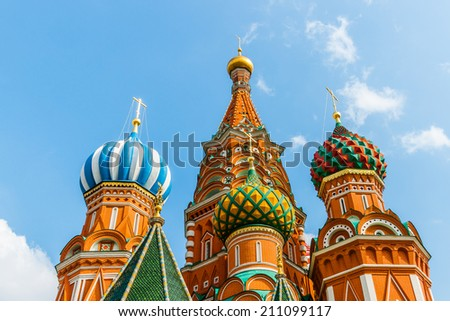 Closeup view of domes of St. Basil's cathedral on Red Square of Moscow against blue sky and white clouds