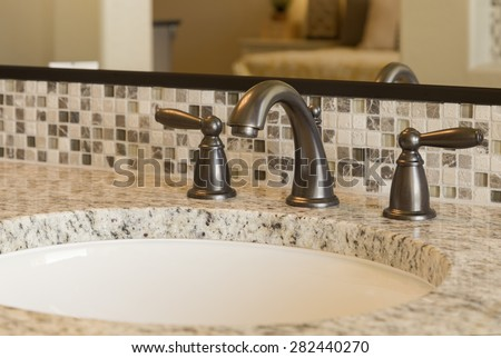 Closeup view of elegant bathroom sink with marble counter top with faucet in focus.   - stock photo