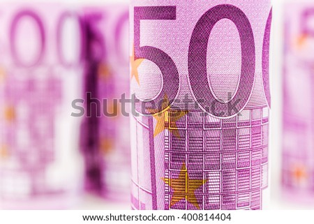closeup view of 500 euro rolled banknote with the background made of another 500 euro banknotes blurred and rolled up - stock photo