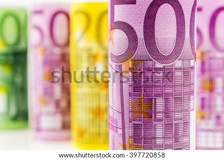 closeup view of 500 euro rolled banknote with the background made of big euro banknotes blurred and rolled up - stock photo