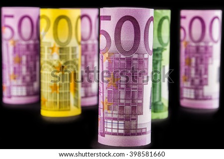closeup view of 500 euro rolled banknote with the background made of 500 euro banknotes blurred and rolled up on black background - stock photo