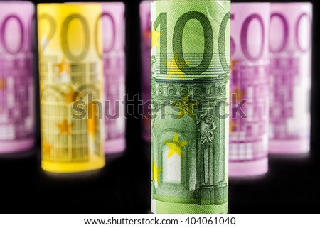 closeup view of 100 euro rolled banknote with the background made of 500 euro banknotes blurred and rolled up on black background - stock photo