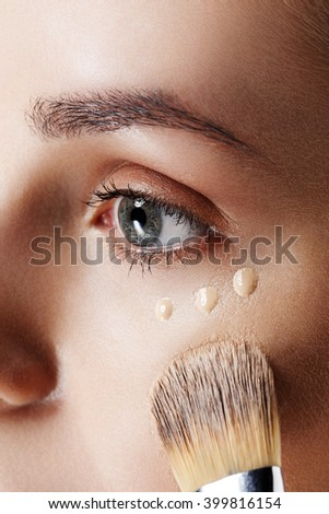 Closeup view of face of Beauty Girl with Makeup Brushes. Natural Makeup for Brunette Woman with blue Eyes. Makeover. Perfect Skin. Ideal for commercial. Part of face - stock photo