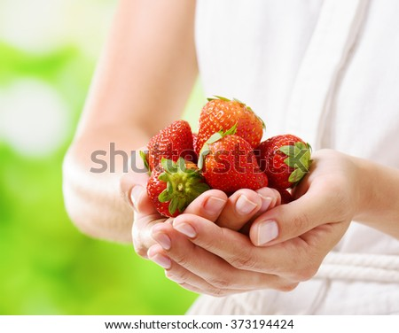 Closeup view of fresh ripe red juicy strawberries in hands of young woman in white dress on nature background. Healthy eco sweet food rich in vitamins. Product of organic farming. - stock photo