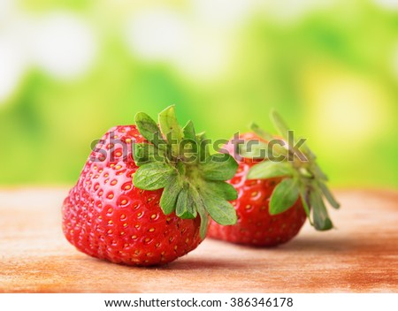 Closeup view of fresh ripe red juicy strawberries on wooden board on nature background. Healthy eco sweet food rich in vitamins. Popular product of organic farming. - stock photo