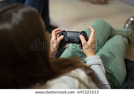 closeup view of gamer girl playing video games with joystick sitting on Bean bag chair and pressing buttons.
