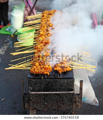 Closeup view of grilled skewered meat on a smoky barbecue pit.  - stock photo