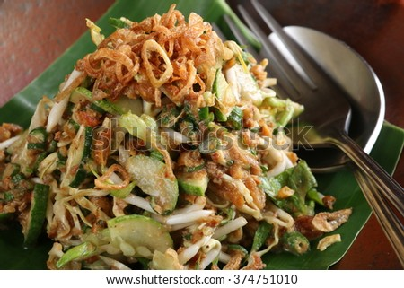 Closeup view of karedok, Sundanese signature raw vegetable salad with peanut dressing. Plated on banana-leaf-lined earthenware dish with a spoon and fork left on the right hand side. - stock photo