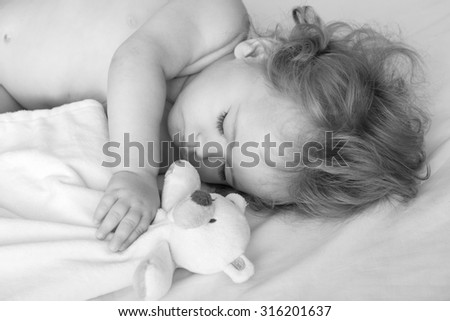 Closeup view of lovely little sleeping boy child with blonde curly hair round cheeks and tiny fingers lying with closed eyes in bed near bear toy black and white, horizontal picture