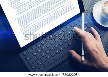 Closeup view of male hands typing on electronic tablet keyboard-dock station. Business information on device screen. Man working at office and using electronic pen.Horizontal