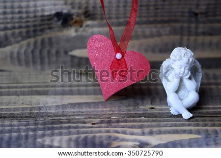 Closeup view of one beautiful cupid angel decorative figurine near red paper greeting valentine card on hanging ribbon with no people on wooden background copy space, horizontal picture - stock photo