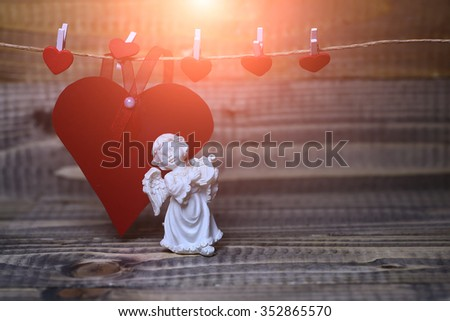 Closeup view of one beautiful cupid angel decorative figurine near red paper greeting valentine card on hanging ribbon on clothes-peg with no people on wood background copy space, horizontal picture - stock photo