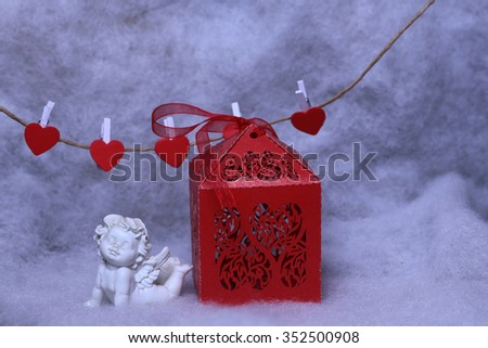 Closeup view of one beautiful cupid angel decorative figurine near red paper greeting valentine box and hanging clothes-peg in shape of heart with white wadding decorating snow, horizontal picture - stock photo