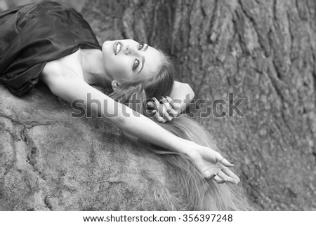 Closeup view of one beautiful sensual sexy young mysterious woman with long lush hair falling down in dress lying on stone in forest outdoor on natural background black and white, horizontal picture - stock photo