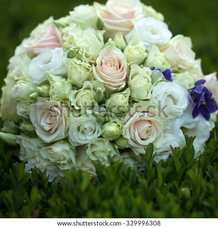 Closeup view of one big round beautiful fresh wedding bouquet of rose flowers pink white and yellow pastel colors lying on green grass sunny day outdoor, square picture