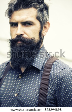 Closeup view of one handsome senior stylish man with black hair and long lush beard in blue shirt standing outdoor on white wall background, vertical picture