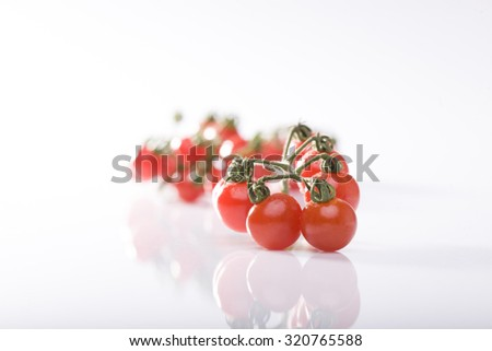 Closeup view of one natural fresh tasty ripe red tomato bunch with green leaves lying in studio on white background, horizontal picture - stock photo