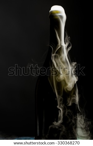 Closeup view of one new open full champagne wive sweet or dry drink green glass bottle with beautiful white smoke for celebration christmas or new year in studio on black background, vertical picture - stock photo