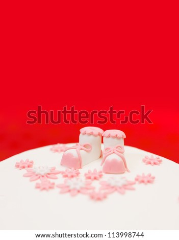 Closeup view of pink topper and flower decoration on baptist cake. Copy space above - stock photo