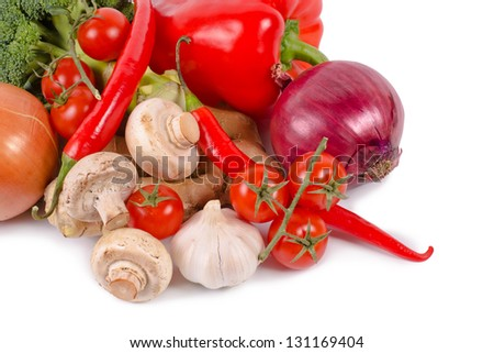 Closeup view of resh farm vegetables including, peppers, tomato, chilli, onions, mushrooms, garlic and broccoli on a white studio background - stock photo