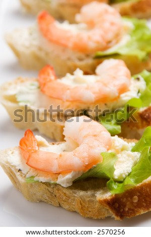 Closeup view of shrimp toasts with salad and garlic cheese (shallow DOF)