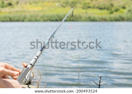 Closeup view of the hand of a man fishing on a lake with a spinning reel and rod looking along the length of the rod - stock photo