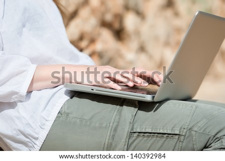 Closeup view of the hands of a young woman typing on her laptop sitting outdoors in sunshine - stock photo