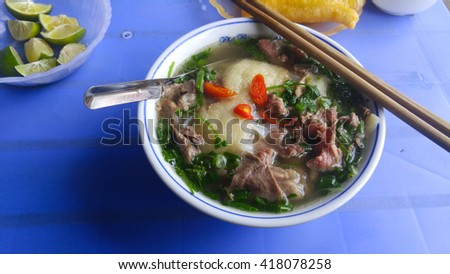 Closeup view of the Pho Bo in street cafe of Vietnam. The Pho Bo is a traditional Vietnamese beef noodle soup with garnish of leaves of cilantro and Asian basil. Popular healthy street food of Asia. - stock photo