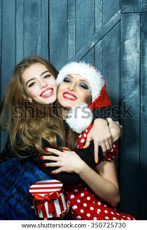 Closeup view of two beautiful brunette young happy smiling embracing new year women celebrating christmas in red santa claus hat with white fur holding gift box indoor, vertical picture - stock photo
