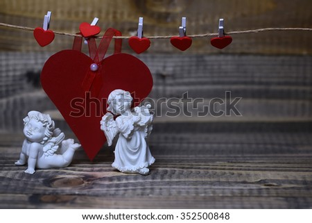 Closeup view of two beautiful cupid angels decorative figurine near red paper greeting valentine card on hanging ribbon on clothes-peg with no people on wood backdrop copy space, horizontal picture - stock photo