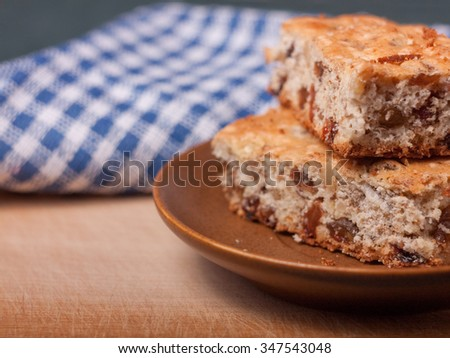Closeup view of two piece of biscuit cake with walnuts and raisins on brown ceramic saucer, with blue plaid cloth on the background. - stock photo