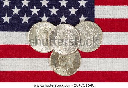 Closeup view of United States Silver Dollar Coins placed on American Flag  - stock photo
