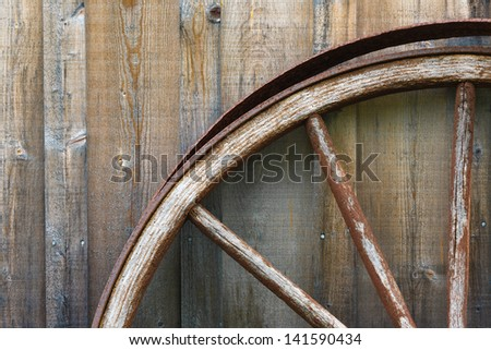 Closeup view of wagon wheel and exterior wooden wall - stock photo