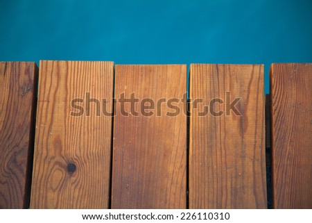 Closeup view of wooden pier with blue sea backdrop - stock photo
