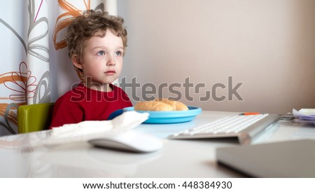 closeup view of young boy playing with computer at night lit by the light form the screen while eating - stock photo